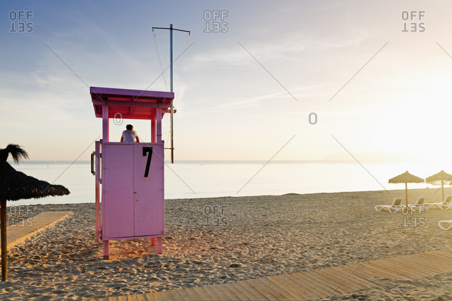 Boy watching the sea from a lifeguard stand