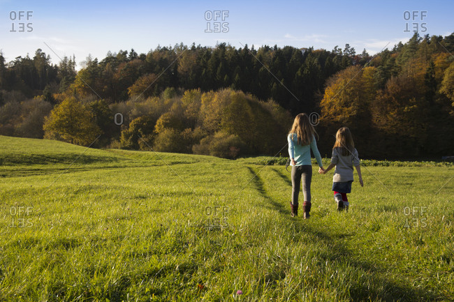 Young girls walking in a meadow in Landshut, Bavaria, Germany