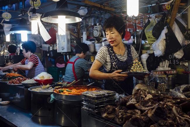 Seoul, South Korea - October 8, 2014: Women selling traditional Korean food inside Gwangjang Market in Seoul, South Korea