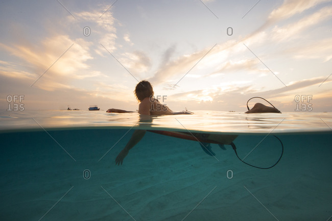 Surfer laying on surfboard in still water