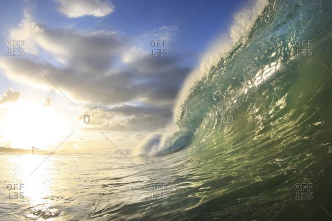 Barrel wave breaking into sea