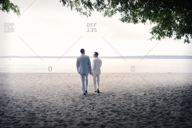 Couple walking on beach in suits