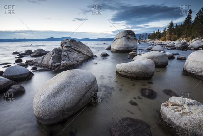 Dusk sets in over the calm waters and granite boulders, east shore of Lake Tahoe, Nevada