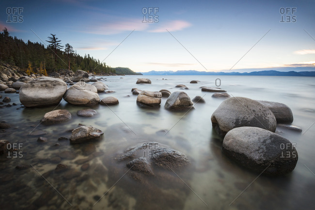 Sunset over calm water and granite boulders on the east shore of Lake Tahoe, Nevada