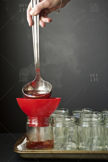 Funneling quince jelly into a jar