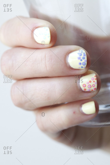 A woman displays her yellow painted nails with dots