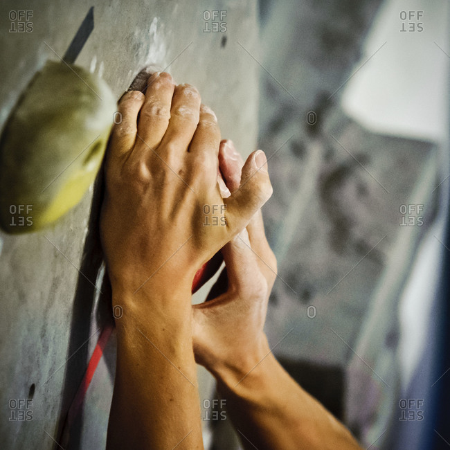 Hands of a climber gripping a hold on an indoor rock wall