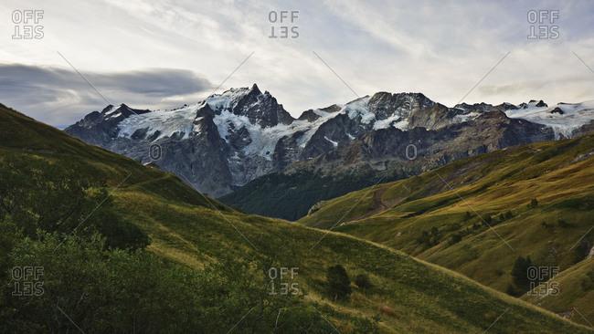 Rolling green hills below the north face of La Meije, Ecrines National Park, France