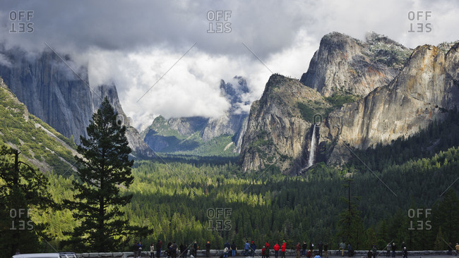 Crowd of tourists watch a clearing storm in Yosemite Valley from Tunnel View, Yosemite National Park, California