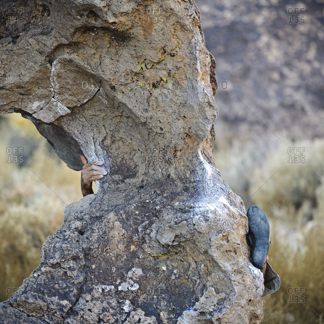Rock climber's hand and foot gripping a boulder, Bishop, California
