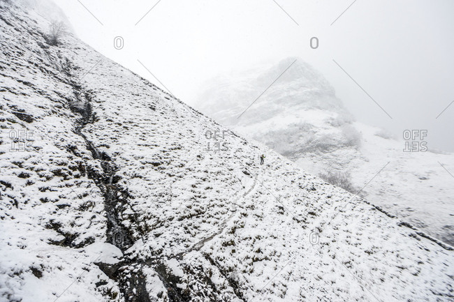 Hiker walking on snowy slopes in a mountainous area of Scotland