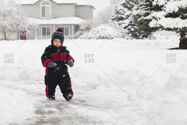 Preschool child walking on snowy sidewalk