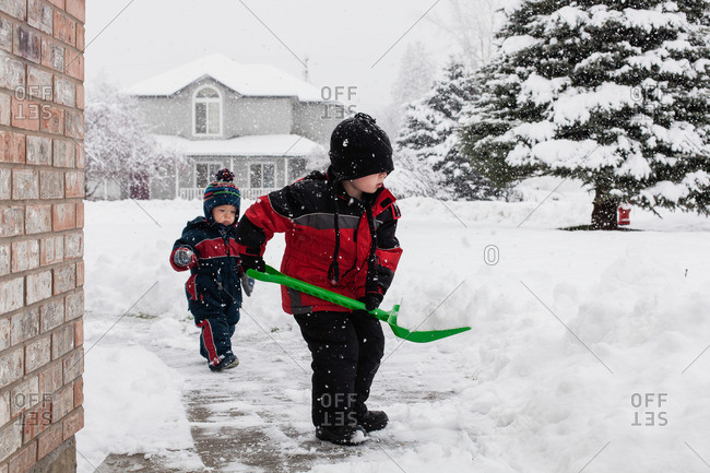 Two young children shoveling snow