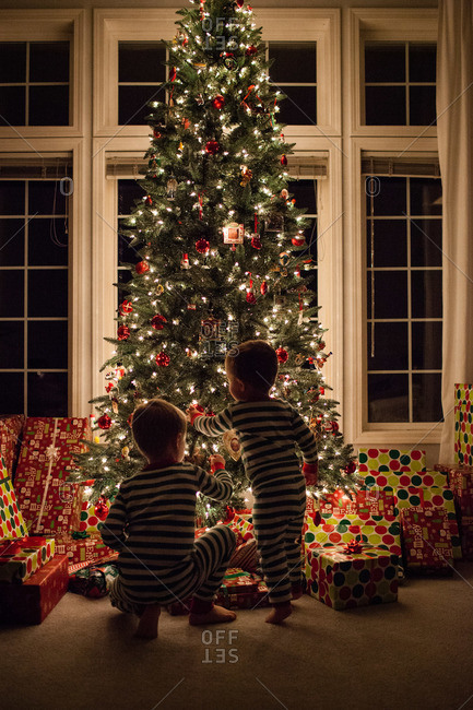 Two young children gaze at gifts in front of Christmas tree