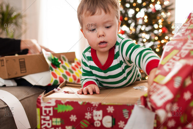 Toddler boy unwraps box on Christmas morning