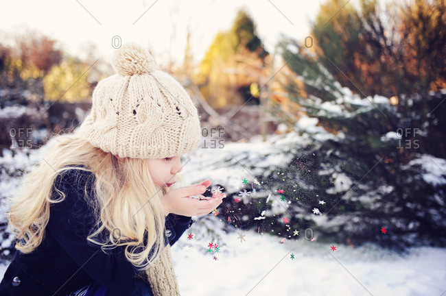 Girl blowing fake snowflakes in snow