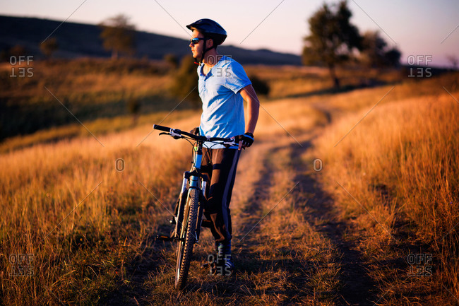 Man on trail with bike watching sunset
