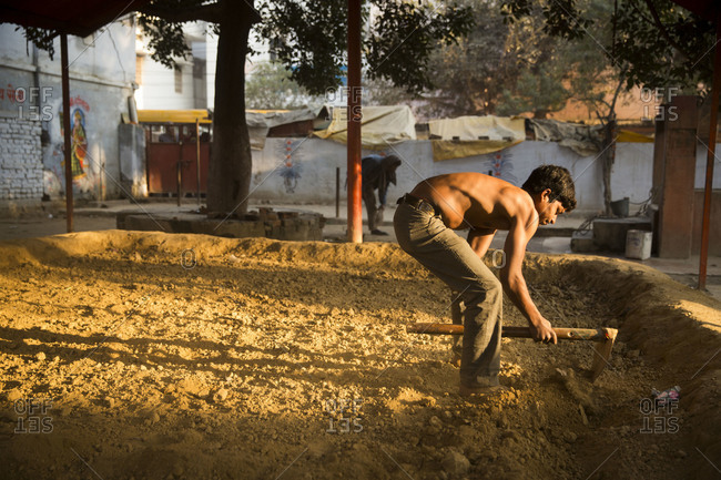 Varanasi, India - March 7, 2014: Kushti wrestler preparing the arena with a hoe, Varanasi, India