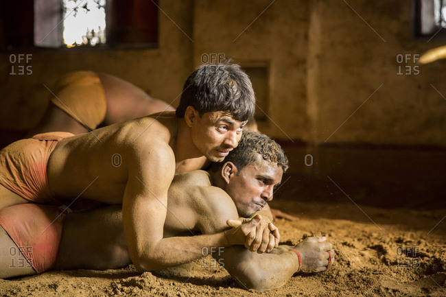 Varanasi, India - March 8, 2014: Kushti wrestler pinning down his opponent, Varanasi, India