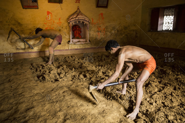 Varanasi, India - March 8, 2014: Kushti wrestlers preparing the arena with a hoe, Varanasi, India