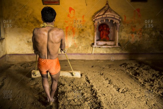 Varanasi, India - March 8, 2014: Back view of Kushti wrestler preparing the arena, Varanasi, India