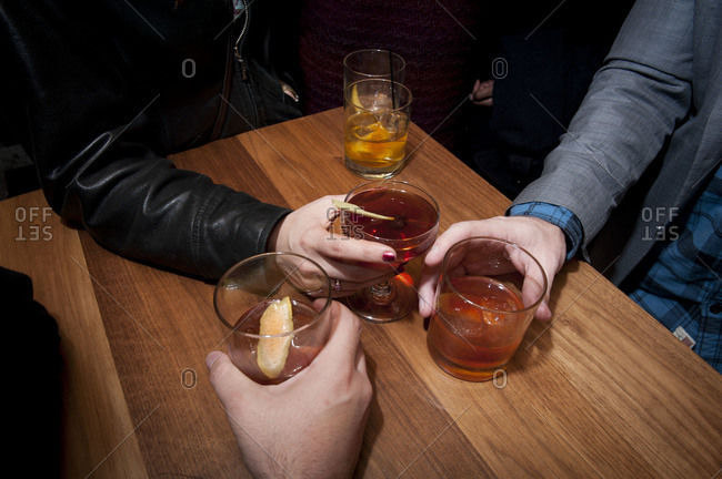 Three hands holding cocktails at a table