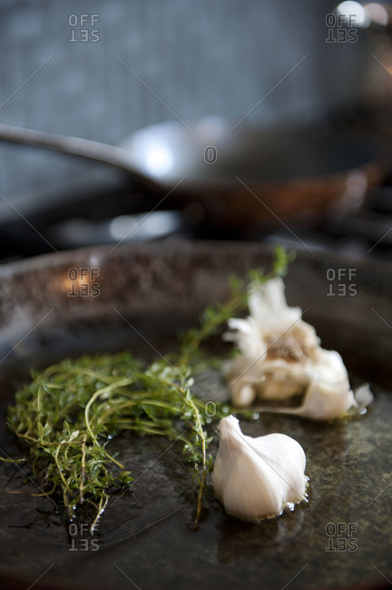 Thyme and whole garlic in a seasoned skillet