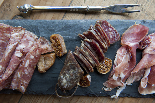 Overhead view of cured meats and figs on slate board