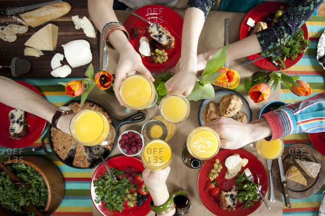 Overhead view of diners' hands toasting with mimosas at brunch