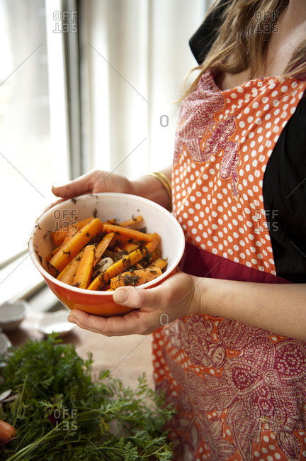 Aproned woman holding a bowl of sliced carrots