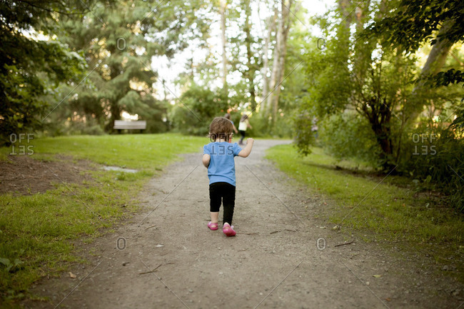 A toddler walks down a path after some children
