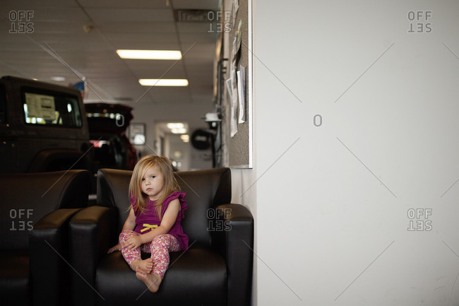 A girl sits on a chair at a car dealership