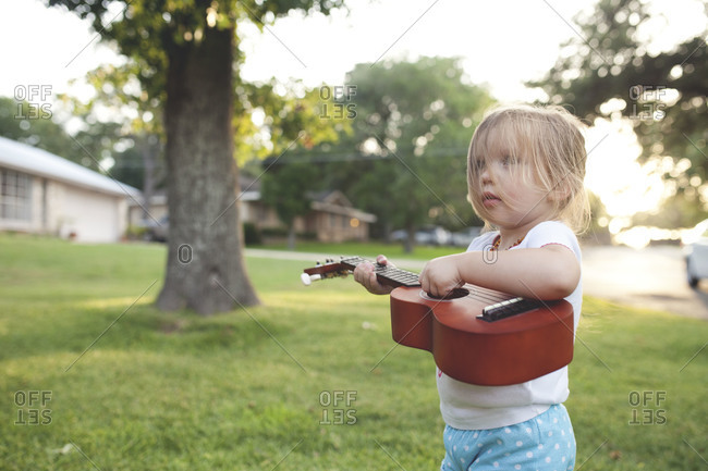 A little girl plays guitar outside