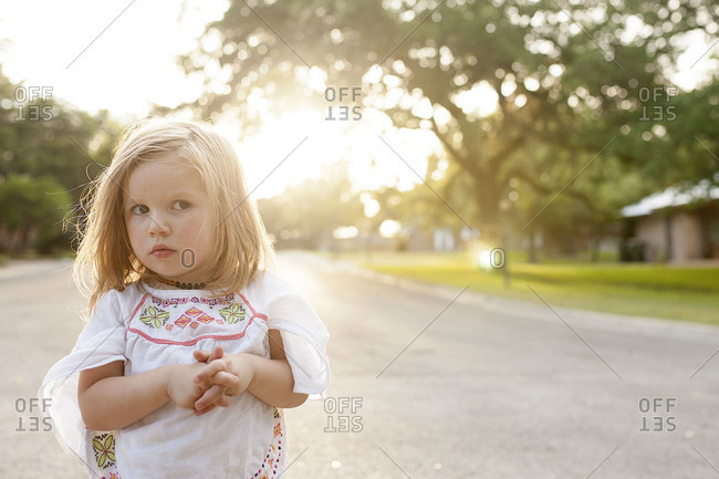 A little girl stands in the street