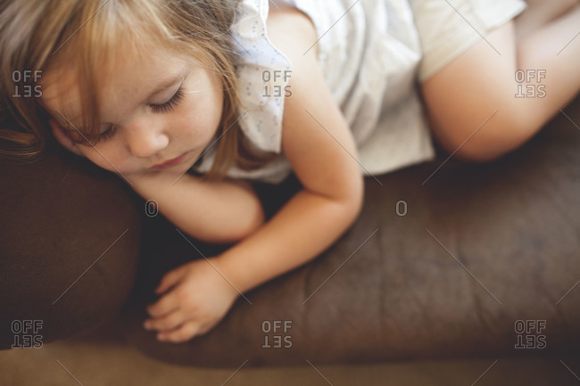 A little girl sleeps on a couch