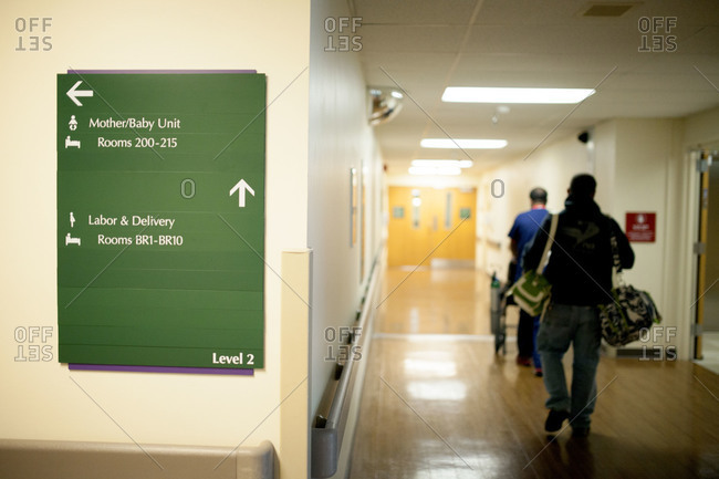 A hospital sign directs people to delivery rooms