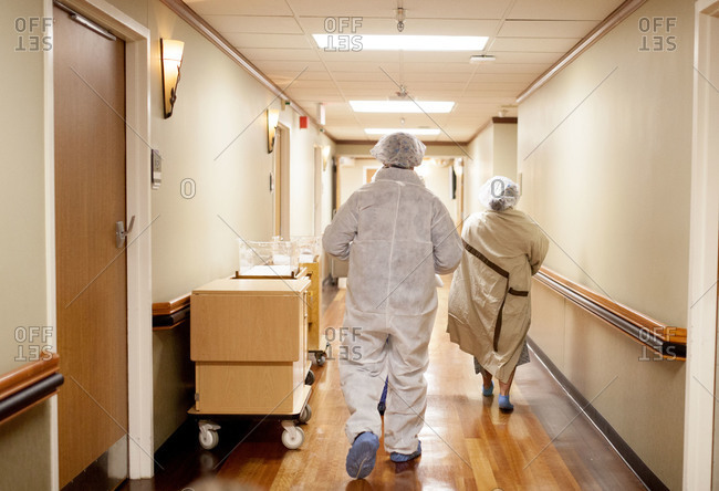 An expectant mother and father in protective surgical gowns head down a hall