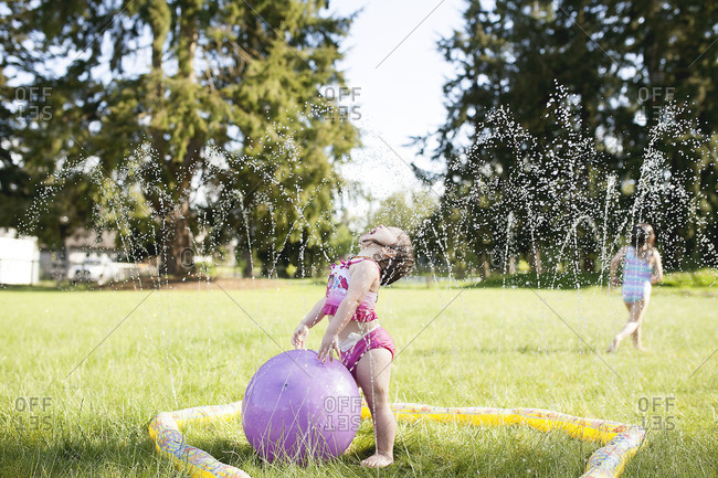 Two little girls play in a sprinkler
