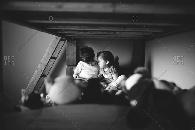 A girl and boy read on the bottom of a bunk bed