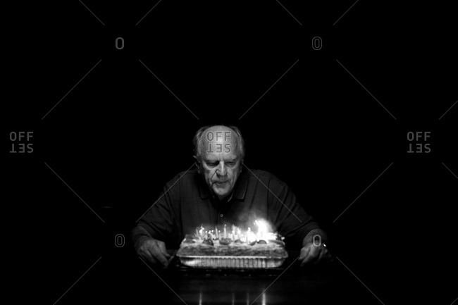 An old man blows out candles on a cake