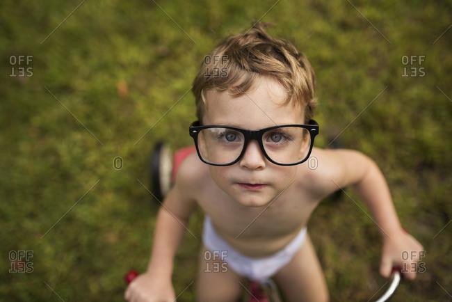 A little boy wears oversized glasses