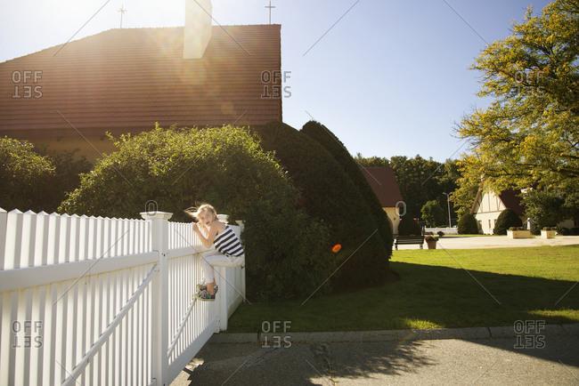 A girl climbs over a fence