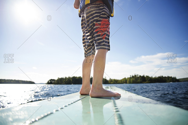 A boy stands on a diving board
