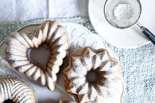 Small bundt cakes served on a plate with confectioners sugar