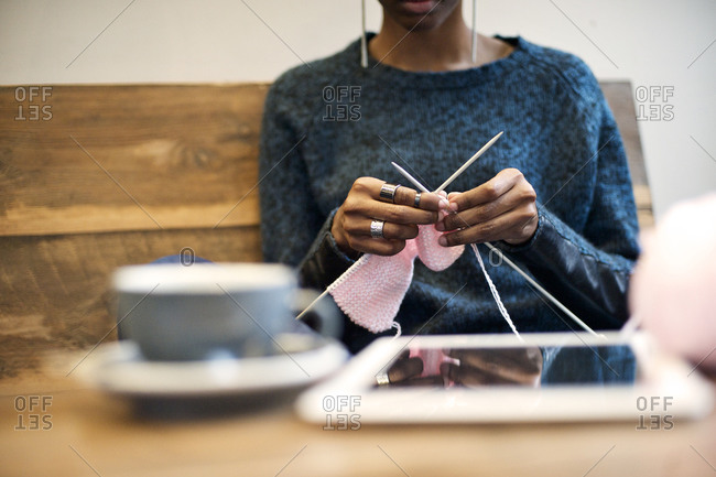 Close up of young woman knitting in a cafe