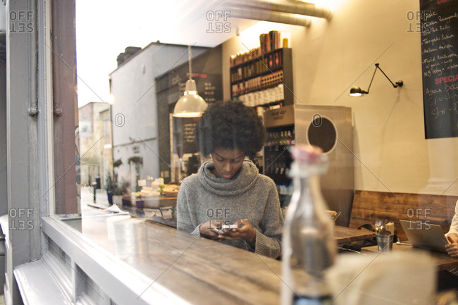 Young woman using her phone in a cafe