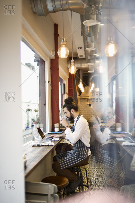 Barista drinking and checking laptop in cafe