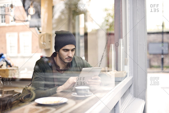 Man working on tablet in a cafe