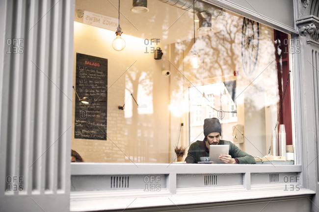 Man sitting in cafe holding tablet