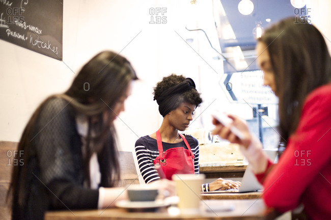 Women using devices in a cafe